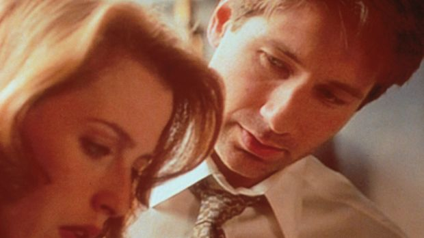 Mulder (David Duchovny, r.) zeigt Scully (Gillian Anderson, l.) ein Video, au...