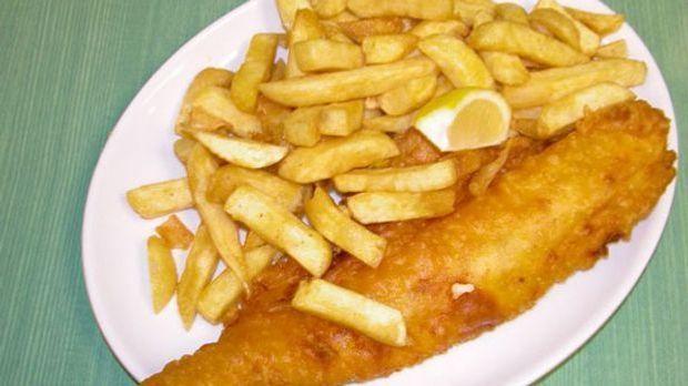 Der knusprig ausgebackene Fisch mit frittierten Kartoffelstäbchen ist ein Kla...