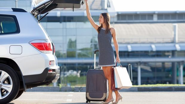 Frau öffnet Kofferraumtür von Auto