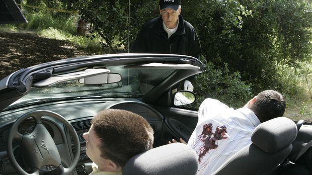 Zwei Navy Lieutnants fahren in einem Cabrio auf einer Landstrasse, als sie vo...