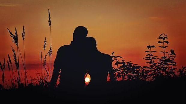 Partner sitzend bei Sonnenuntergang